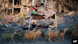 11일 가자지구에서 이스라엘의 공습으로 파괴된 건물 주변에 주민들이 천막을 치고 앉아있다.