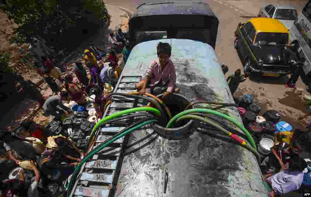 An Indian boy sits atop a government water supply truck as residents fill water containers in New Delhi. Residents have been struggling with water shortages for the past few days after the upper Ganga Canal was shut for repairs.