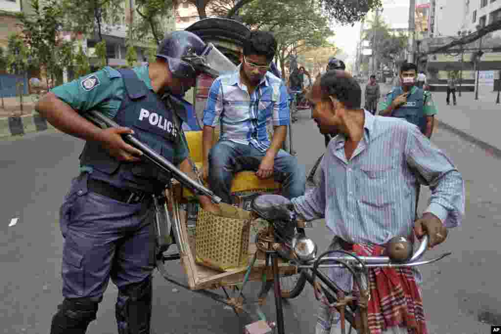 A police officer searches a passerby during a nationwide strike in Dhaka, Bangladesh, March 4, 2013.