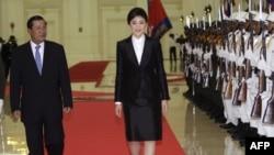 Thủ tướng Campuchia Hun Sen (trái) và Thủ tướng Thái Lan Yingluck Shinawatra duyệt hàng quân danh dự tại Peace Palace ở Phnom Penh, ngày 15/9/2011