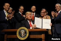 U.S. President Donald Trump is applauded after signing an Executive Order on U.S.-Cuba policy at the Manuel Artime Theater in Miami, Florida, June 16, 2017.