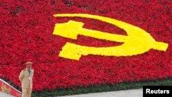 Một cảnh sát đứng canh bên cạnh biểu tượng của Cộng sản được trang trí bằng hoa tại Trung tâm Hội nghị Quốc gia, địa điểm tổ chức Đại hội Đảng lần thứ 11, tại Hà Nội ngày 12/1/2011.