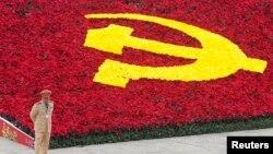 Một cảnh sát đứng bảo vệ bên cạnh logo đảng cộng sản được trang trí bằng hoa tại Trung tâm Hội nghị Quốc gia, Hà Nội.