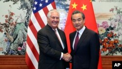 U.S. Secretary of State Rex Tillerson, left, shakes hands with Chinese Foreign Minister Wang Yi before their meeting at the Great Hall of the People in Beijing, Sept. 30, 2017.