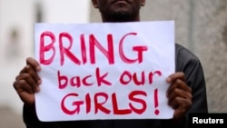 """Seorang pria membawa kertas bertuliskan """"Kembalikan Anak-anak Perempuan Kami"""" dalam sebuah aksi di Cape Town, Afrika Selatan, untuk mendukung siswi-siswi yang diculik kelompok militan Boko Haram di Nigeria (8/5)."""
