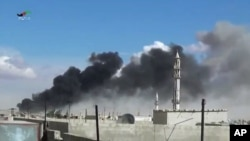Smoke rises after airstrikes by military jets in Talbisseh, a city in western Syria's Homs province, where Russia launched airstrikes for the first time, Sept. 30, 2015. The image was made from video provided by Homs Media Center and authenticated by AP.
