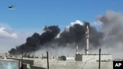 Smoke rises after airstrikes by military jets in Talbiseh, a city in western Syria's Homs province, where Russia launched airstrikes for the first time, Sept. 30, 2015. The image was made from video provided by Homs Media Center and authenticated by AP.