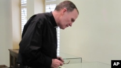 The Very Rev. David M. O'Connell examines the etching he discovered in a bathroom cabinet