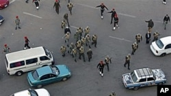 Military police and soldiers walk among traffic as they clear remaining protesters in Tahir square in Cairo, Egypt. Egypt's military rulers dissolved parliament Sunday, suspending the constitution and promising elections in moves cautiously welcomed by pr