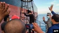 BAKAMLA melepaskan ABK kapal tanker Iran MT Horse untuk menaiki kapal mereka di lepas pantai Kepulauan Riau, sebelum meninggalkan perairan Indonesia, 29 Mei 2021. (BAKAMLA/AFP)