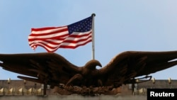A United States flag is seen flying above an eagle atop a U.S. embassy building (file photo).