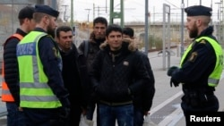 FILE - Swedish police officers speak to a group of people at the Hyllie train station near Malmo, Sweden, Nov. 12, 2015.