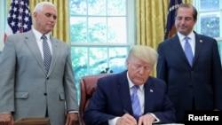 特朗普總統在彭斯副總統和衛生與公共服務部部長阿扎爾的簇擁下在白宮橢圓形辦公室簽署《納稅人優先法》。(2019年7月1日)