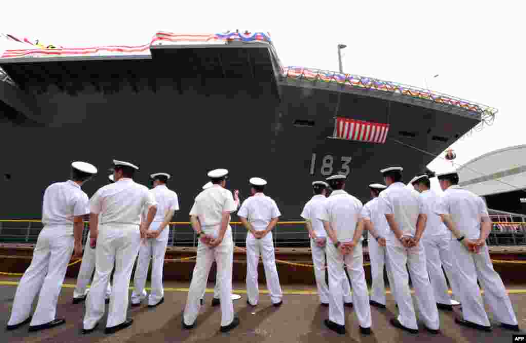 Crew members of Japan's newest warship stand along the vessel during a launch ceremony in Yokohama, August 6, 2013.