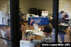 In this Feb. 8, 2020, photo, people volunteer to get people registered to vote and a booth offering employment for the upcoming 2020 census stands in the background, during the celebration of the town's 45th year since it was incorporated, in Guadalupe, A
