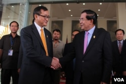 Cambodia's Prime Minister Hun Sen (R) shakes hand with Sam Rainsy (L) president of the Cambodia National Rescue Party (CNRP), after the National Assembly's vote to select the members of National Election Committee in Phnom Penh, Cambodia on April 9th, 2015.