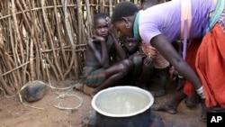 In this photo taken Tuesday, Oct. 17, 2017, a Karamojong woman prepares a meal at her village in the semi-arid savannah region of Karamoja, in northeastern Uganda. (AP Photo/Adelle Kalakouti)