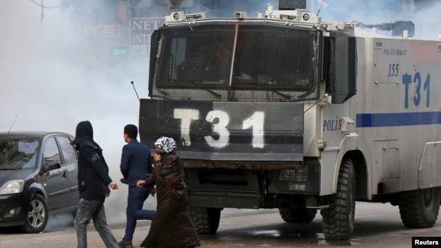 People walk past an armored police vehicle as Turkish riot police use tear gas to disperse Kurdish demonstrators during a protest against a curfew in Sur district and security operations in the region, in the southeastern city of Diyarbakir, Turkey, Jan.
