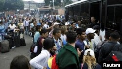 Migrantes venezolanos tratan de abordar un bus que los lleve a la frontera con Colombia desde la frontera San Cristóbal, en Venezuela.