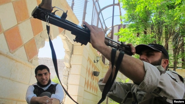A Free Syrian Army fighter inspects his weapon in the Khan al-Assal area near Aleppo, April 27, 2013.