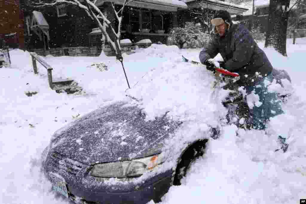 برف سنگین در آمریکا. این مرد سعی دارد ماشین خود را از برف در میسوری آمریکا خارج کند. در مرکز و شرق آمریکا برف مردم را غافلگیر کرد.