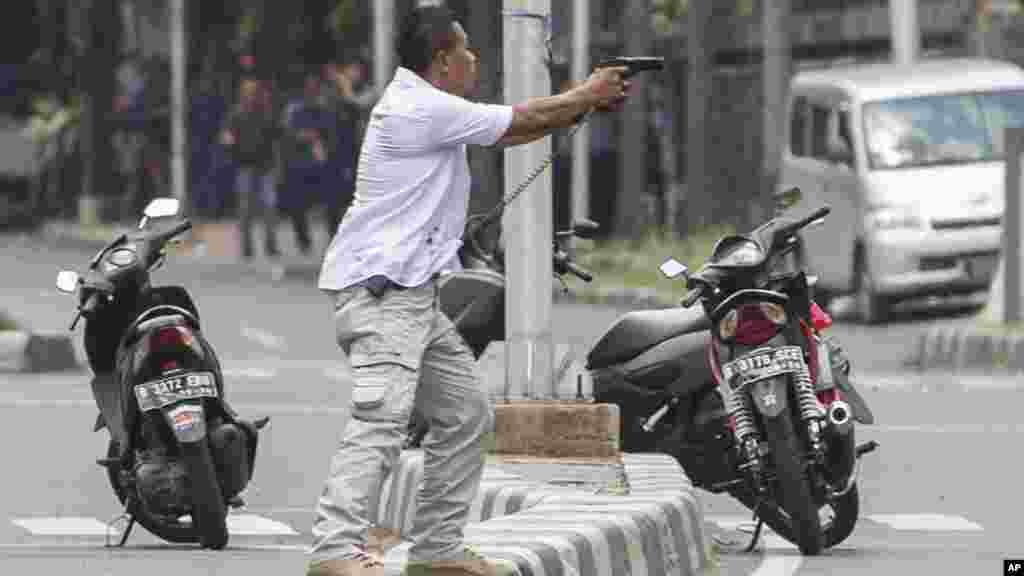 Askari kanzu akiwa ameelekeza bunduki yake kwa washambuliaji wakati wa mapambano ya bunduki mara baada ya mlipuko huo Jakarta, Indonesia, Jan. 14, 2016.