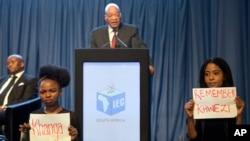 ພວກປະທ້ວງສອງຄົນ ຖືປ້າຍ ຂະນະທີ່ປະທານາທິບໍດີ Jacob Zuma ກ່າວຖະແຫລງ ການປະກາດ ຜົນຂອງການເລືອກຕັ້ງ ຂັ້ນເທດສະບານ ໃນນະຄອນຫຼວງ Pretoria ຂອງອາຟຣິກາໃຕ້, ວັນທີ 6 ສິງຫາ 2016. ພວກປະທ້ວງໝາຍເຖິງ ຄະດີການຟ້ອງຮ້ອງ ຂົ່ມຂືນສຳເລົາ ໃນປີ 2006 ຂອງທ່ານ Zuma ທີ່ສານໄດ້ຕັດສິນ ໃຫ້ພົ້ນຈາກໂທດ.