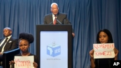 FILE - Protesters hold up signs as President Jacob Zuma speaks at the announcement of the results of municipal elections in Pretoria, South Africa, Aug. 6, 2016. The protest refers to Zuma's acquittal for rape in 2006.