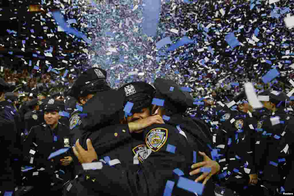 Members of the class of the New York City Police Academy embrace during their graduation ceremony at Madison Square Garden in New York.