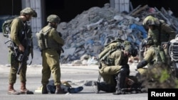 El cuerpo de un palestino que achuchilló a un soldado israelí yace en el suelo luego de ser abatido en Hebrón.