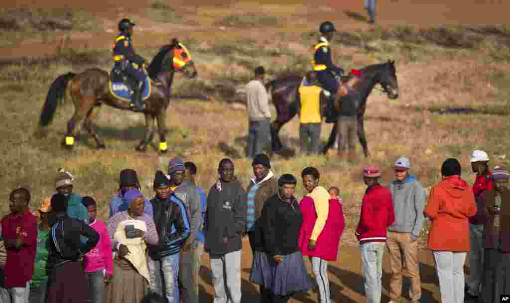 South Africans queue to vote as mounted police provide security near a polling station that was burned down overnight. A tent was erected to replace the station in the politically sensitive mining town of Bekkersdal, South Africa, May 7, 2014.