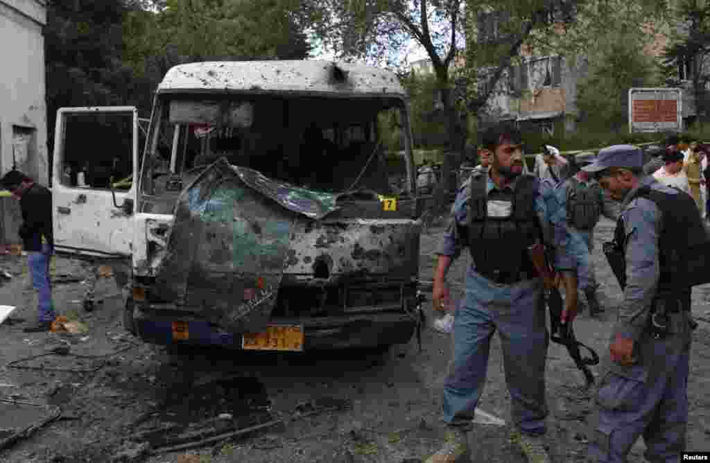Afghan police stand at the site of a suicide car bomb attack in Kabul, June 11, 2013.