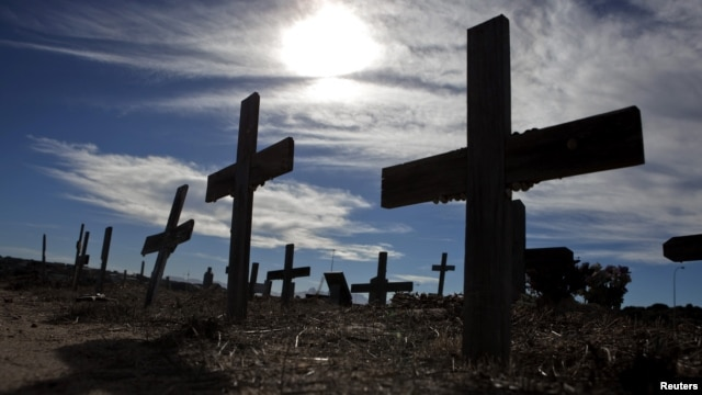 Crosses fill a graveyard in Cape Town's Khayelitsha township February 27, 2010. Many of those buried in the South African cemetery died from AIDS or related complications such as tuberculosis (TB).