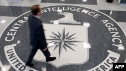 FILE - A man crosses the Central Intelligence Agency logo in the lobby of CIA Headquarters, Langley, Virginia.