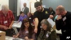 維吉尼亞州紐波特紐斯的選務官員在州眾議員選舉的重新計票過程驗看電腦無法掃描的選票。 (2017年12月19日)