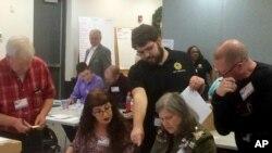 维吉尼亚州纽波特纽斯的选务官员在州众议员选举的重新计票过程验看电脑无法扫描的选票。(2017年12月19日)