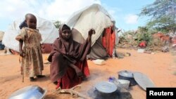 FILE - Kadija Mohamed cooks food for her children in a camp set up for internally displaced people in Dinsoor in southern Somalia, Jan. 5, 2012.