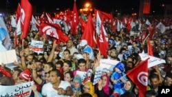 Para pendukung partai Islamis Ennahda melambaikan bendera dan berbagai spanduk sambil meneriakkan slogan mereka dalam aksi demo di Tunis, Tunisia (3/8).
