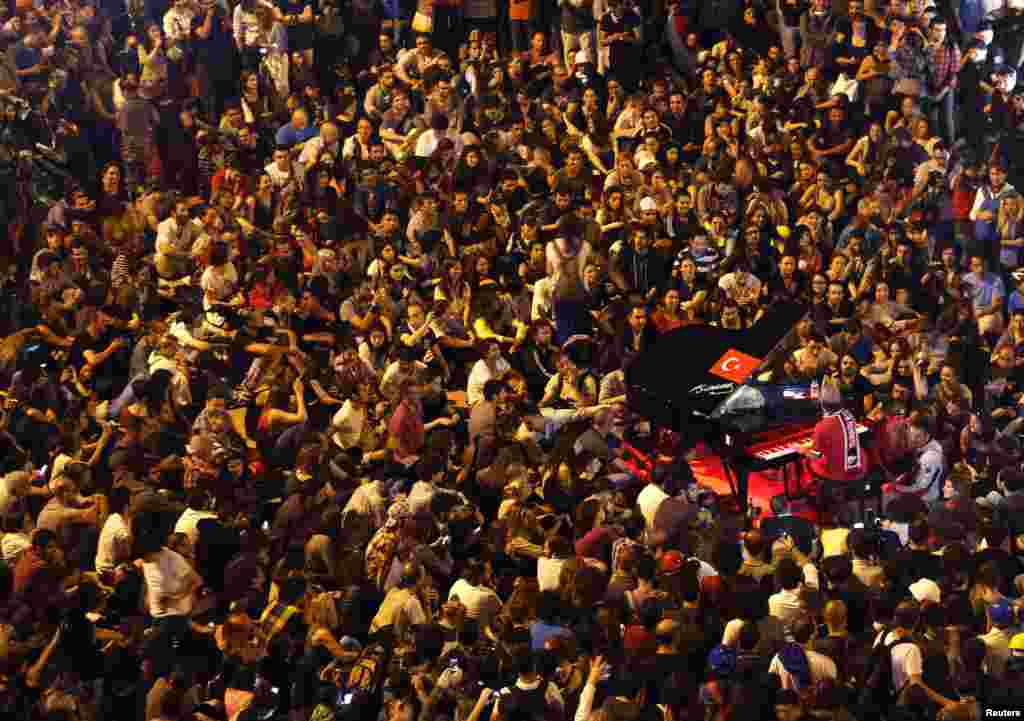 German pianist Davide Martello is surrounded by anti-government protesters as he performs in Istanbul's Taksim Square, June 13, 2013.