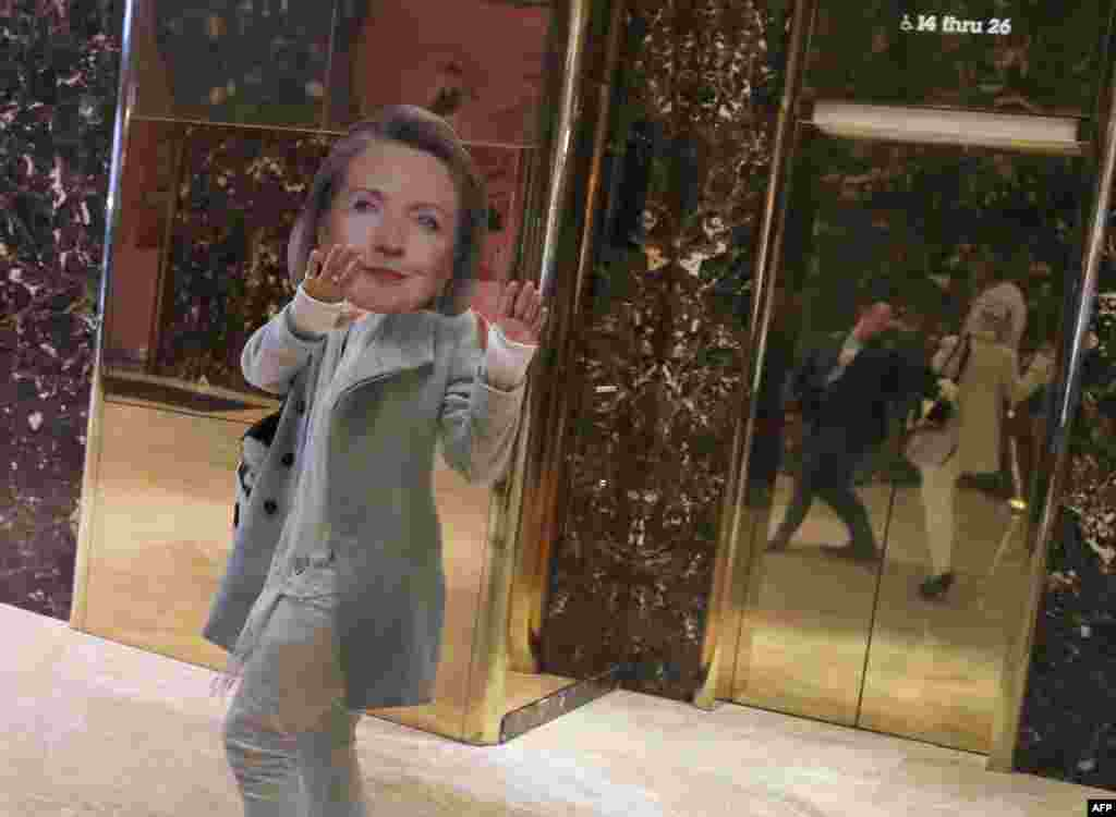 A man wearing a Hillary Clinton mask walks through Trump Tower in New York.