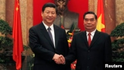 FILE - China's Vice President Xi Jinping (L) poses for a photo with Vietnam's Communist Party's Senior Politburo member Le Hong Anh in front of a bust of late Vietnamese revolutionary leader Ho Chi Minh at the Presidential Palace in Hanoi, Dec. 21, 2011.