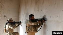 """伊拉克安全部队以墙壁为掩护在摩苏尔已被同""""伊斯兰国""""交战。(2016年12月30日)."""