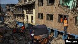 카트만두 외곽에서 지진 생존자들이 잔해 밑 물건들을 찾고 있다.