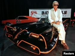 "FILE - Actor Adam West, who portrayed the title character in the 1960s television series ""Batman,"" poses atop the original Batmobile used in the show."