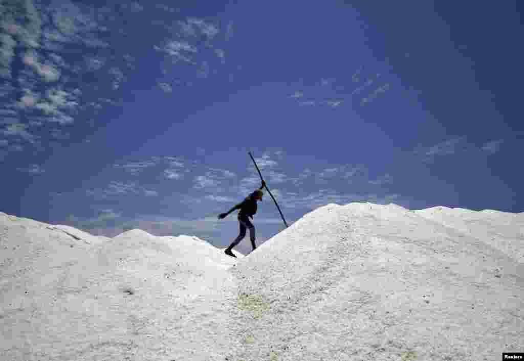 Seorang pria bekerja di sebuang ladang garam di Chennai, India.