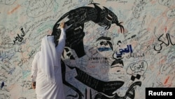 A man writes on a painting depicting Qatar's Emir Sheikh Tamim bin Hamad Al-Thani in Doha, Qatar, July 2, 2017. The artwork has attracted comments of support from residents amid a diplomatic crisis between Qatar and neighboring Arab countries.