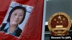 FILE - A picture of Chinese journalist Gao Yu is displayed during a protest calling for her release, outside the Chinese liaison office in Hong Kong, May 11, 2014.