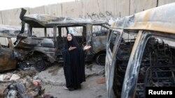 Seorang perempuan menunjukkan lokasi pemboman di distrik Shaoula, Baghdad, Minggu (12/10).