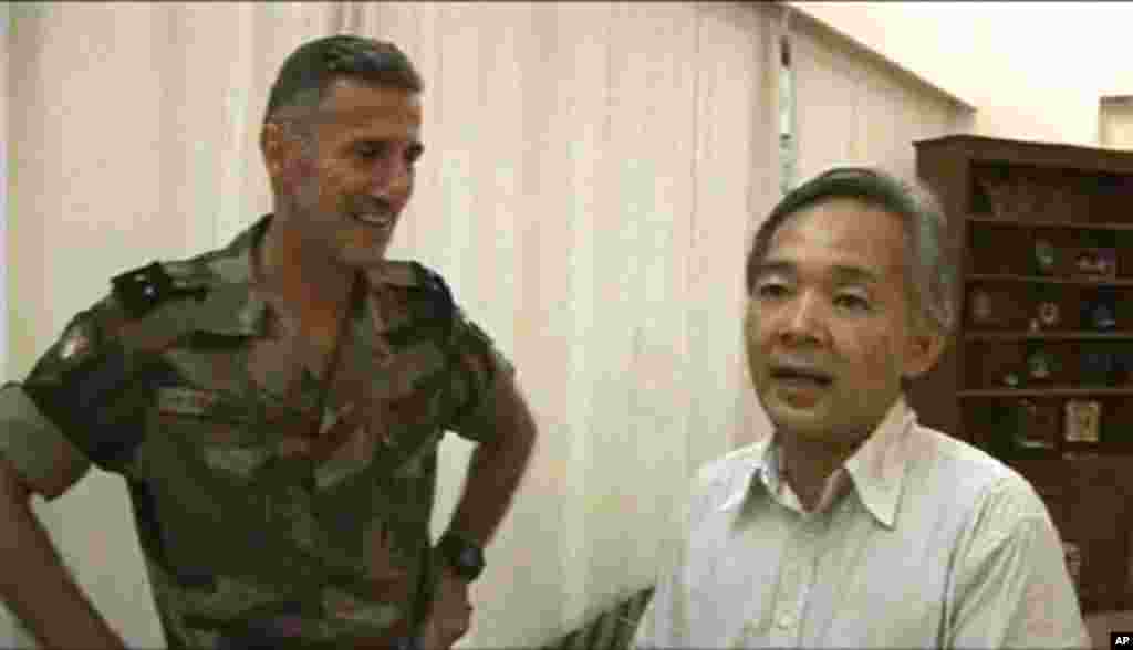 This image taken from a video provided by the French military Thursday April 7, 2011 shows Yoshifumi Okamura, right, the Japanese ambassador to Ivory Coast thanking an unidentified French officer of the Licorne operation, left, following a rescue mission