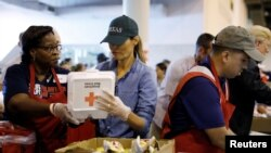 FILE - First lady Melania Trump helps a volunteer hand out meals during a visit with flood survivors of Hurricane Harvey at a relief center in Houston, Texas, Sept. 2, 2017.
